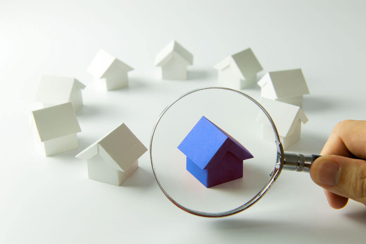 Magnifying glass looking at a small blue model house