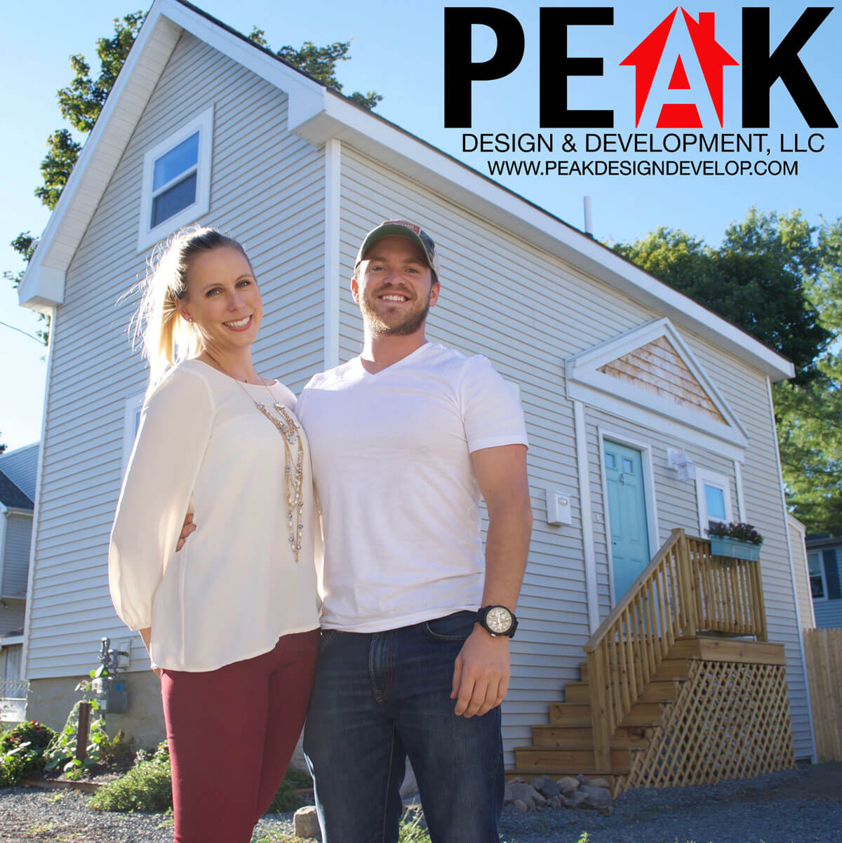 Man and woman standing in front of a renovated house